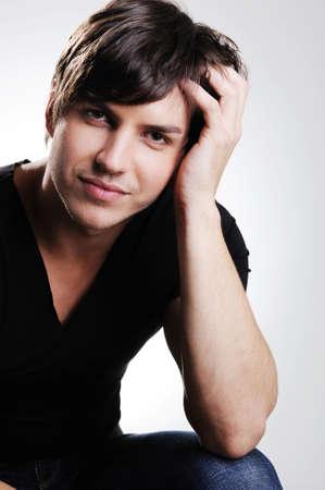 poses de modelos: Retrato de un hombre adulto de belleza posando en el estudio. Tipo muy sentado en la silla