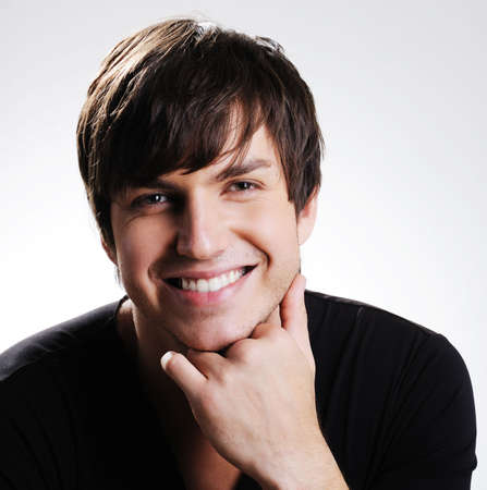 Portrait of a  pretty caucasian young guy with bright toothy smile photo