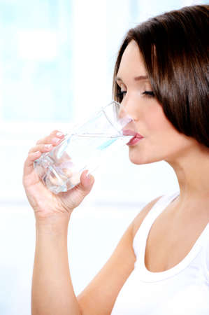 Beautiful young girl drinks pure water from a transparent glass photo