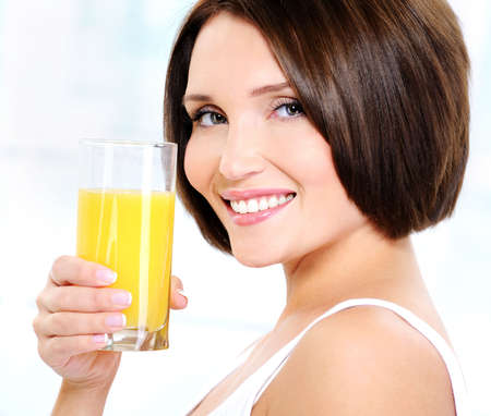 Young beautiful smiling woman holding glass of orange juice photo