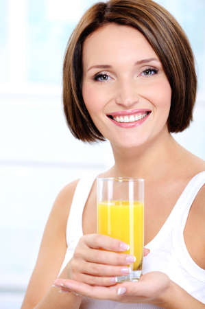 Young beautiful cheerful young adult girl holding glass of fresh orange juice photo
