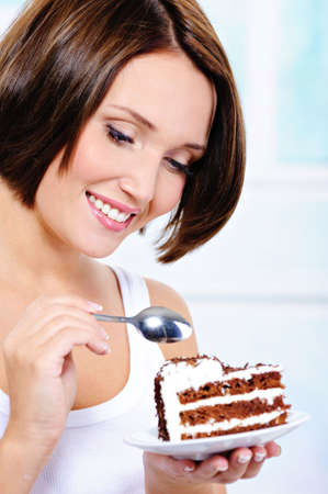 woman eating cake: The beautiful young woman with a spoon in hands is going to eat a sweet pie