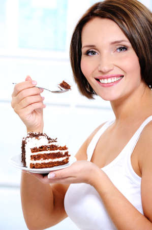 brings: The attractive smiling young girl with a sweet cake slice on a plate brings a spoon to a mouth