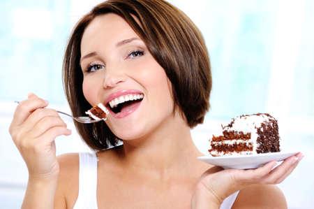 trozo de pastel: Retrato de una mujer feliz y alegre, joven y bella come una torta dulce Foto de archivo