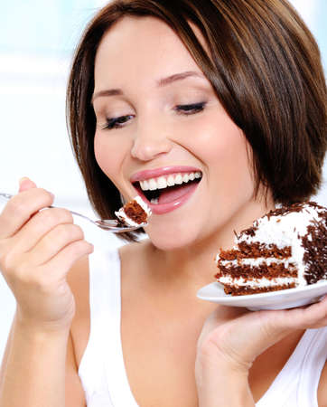 Young pretty girl eats cake on a plate brings a spoon to a mouth