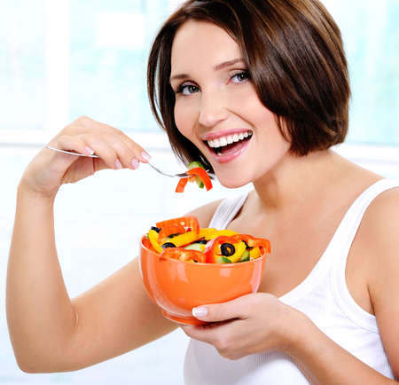 Beautiful smiling young woman eats vegetable salad photo