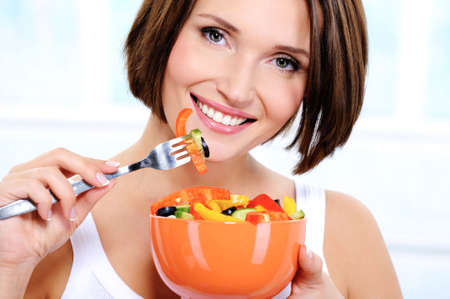The beautiful smiling young woman with a plate of fresh vegetable salad in hands photo