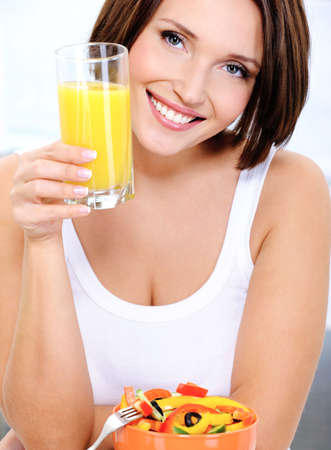 Front view portrait of beautiful smiling female has breakfast salad from vegetables with orange juice Stock Photo
