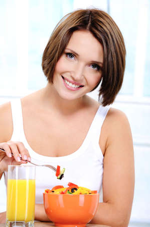 Pretty young smiling female of cute appearance eats vegetable vegetarian salad photo