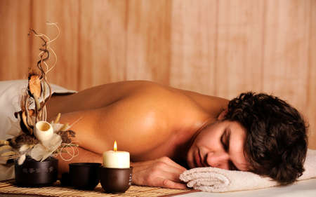 angle view: Young handsome man relaxing in spa salon - high angle view