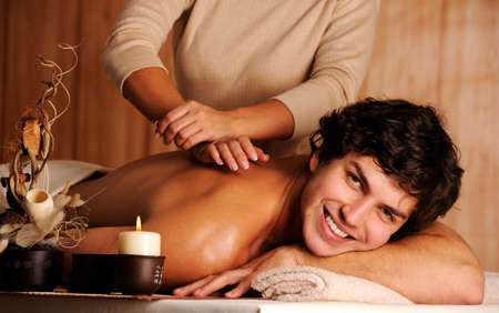 adult massage: Masseur doing massage a handsome happy young man