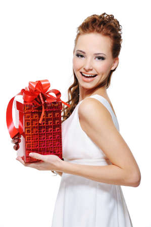 Pretty young laughing woman holding the gift over white background photo