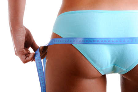 woman buttocks: Woman measures a buttocks with measurement tape. Rear view. Isolated on white. Close-up shot.