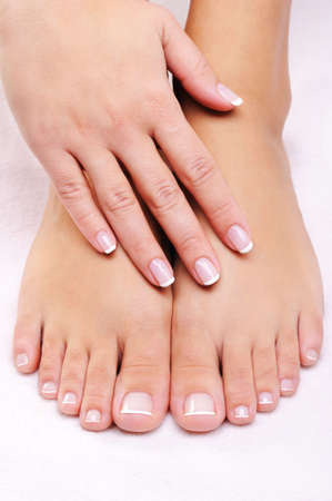 toenail: female hands on the well-groomed feet with french pedicure Stock Photo