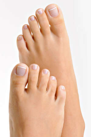 footcare: Beautiful well-groomed female feet with the French pedicure. Isolated on white.  Stock Photo