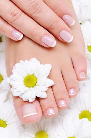 pedicure: mano femmina con bella french manicure sul piede pulito e puro