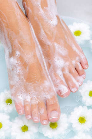 Spa treatment of a beautiful female feet in water photo