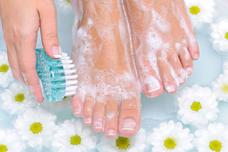 The young woman washes and cleans the beautiful well-groomed legs in water by means of a clearing brush  Stock Photo