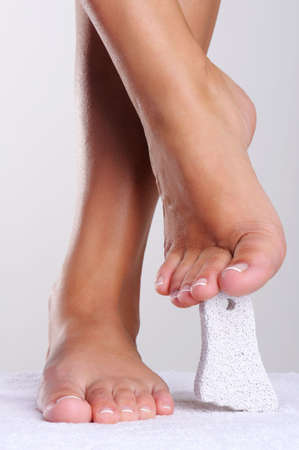 female feet: Pure and well-groomed womans feet  with a pedicure cleaning pumice Stock Photo