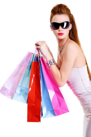 Portrait of the beautiful fashionable cool female with shopping bags after shoppings. Over white background photo