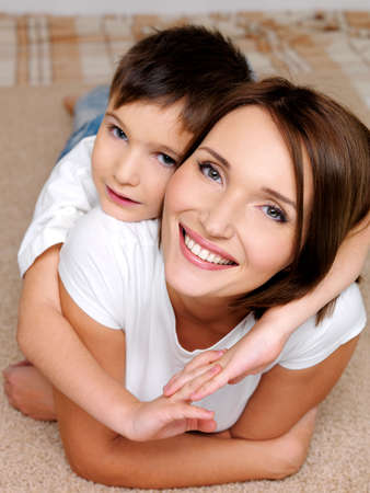 Portrait of an attractive young  happy smiling  mother  with her little son lying on her back