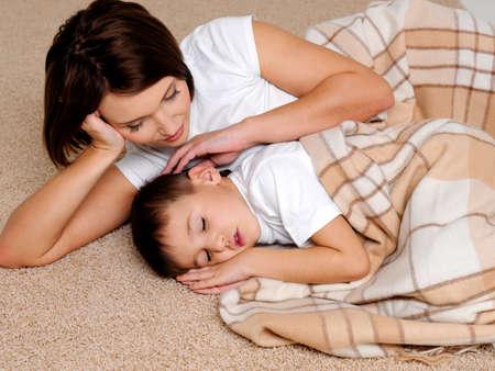 ni�os contentos: Cuidado de los j�venes madre cerca al hijo peque�o para dormir que est� cubierto por un c�lido plaid