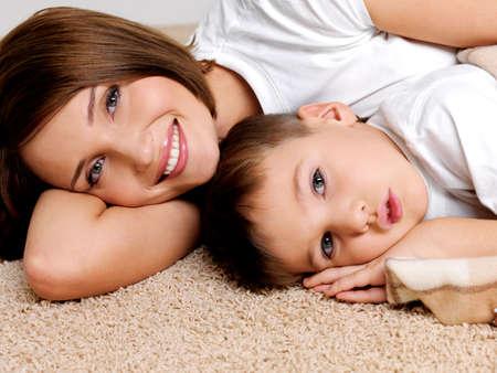 mama e hijo: Retrato sonriente de la madre y el ni�o acostado en un piso en el apartamento de feliz