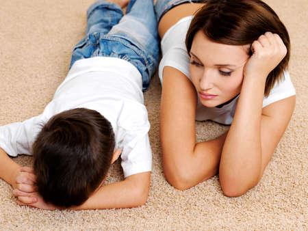crying boy: Foto de la joven madre y su hijo llorando culpable desobediente, acostado en el suelo Foto de archivo