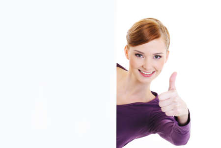 thumbsup: The young beautiful joy woman looks out because of  blank white advertising banner with thumbs-up gesture