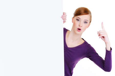 Pretty young Woman look out from blank billboard with lift forefinger up. Idea concept photo