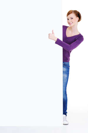 Full-length portrait of a young woman looks out because of empty billboard with thumbs-up  sign Stock Photo - 5971209