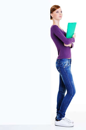 The young beautiful female student with quiet emotion on her face standing near the empty billboard Stock Photo - 5971217
