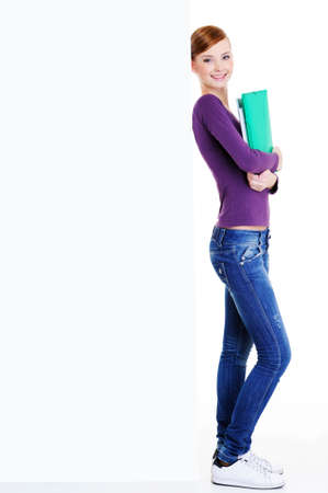 Happy female student with  standing near the blank big banner - isolated on white photo
