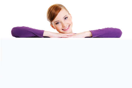 Face of the young beautiful smiling woman above the white blank banner Stock Photo - 5971210
