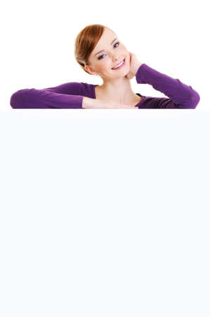 The nice smiling adult female person is over an empty publicity board - On a white background  photo