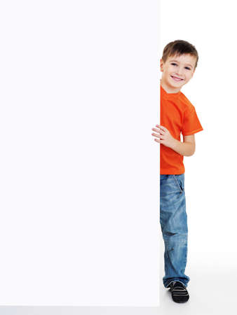 young happy smiling little boy look outs from the blank banner. Fill-length portrait photo