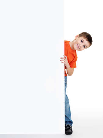 young happy smiling little boy look outs from the blank billboard. Fill-length portrait. Isolated on white photo