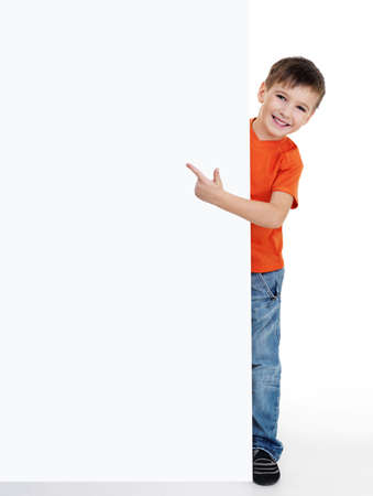 kid pointing: little happy smiling  boy look outs from the empty banner and points on it. Fill-length portrait