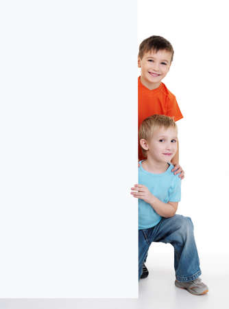 Two  happy smiling little boys look outs from the white billboard on a white background photo