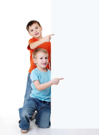ni�os con pancarta: Patronales de mirada de dos ni�os poco alegre de la cartelera y apuntando en �l. Retrato de relleno-longitud Foto de archivo