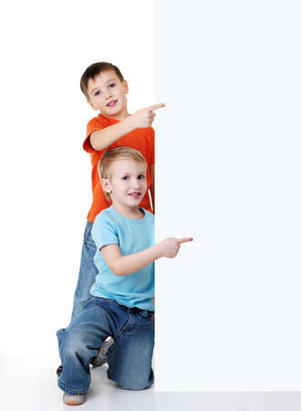 Two cheerful little boys look outs from the billboard and pointing on it. Fill-length portrait photo