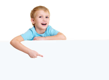 Cute laughing little boy is above on a white blank poster and points on it. photo