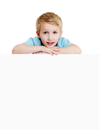cute smiling little boy is above on the empty white placard. isolated on white photo