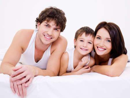 Portrait of the Beautiful young happy family lying in bed photo