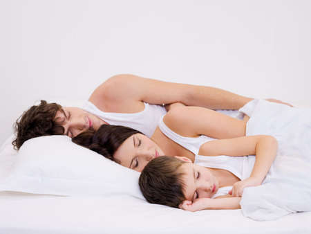 Young beautiful Sleeping family with the little son photo