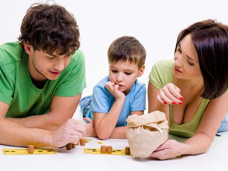 bingo: Los padres j�venes de felices jugando en interiores con peque�o hijo  Foto de archivo