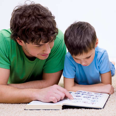 fatherhood: Father and son indoors reading book lying on floor