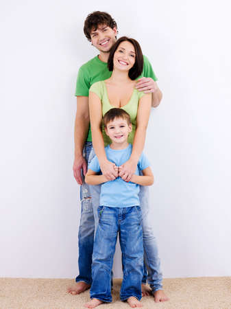women hugging: three person of the young happy smiling family looking at camera Stock Photo
