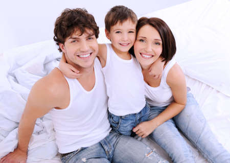 High angle portrait of the Happy parents with little child sitting on a bed photo