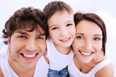 Caras hermosas y alegres de las personas. Una familia feliz de jóvenes de tres personas Foto de archivo - 6068250